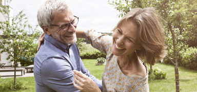 Two adults dance and laugh in an outdoor setting.