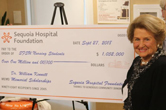 Photograph of Gloria Kennett with oversized check for $1 million.