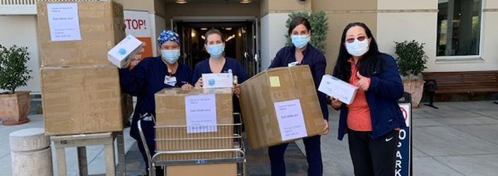 Photo of nurses holding PPE supplies.