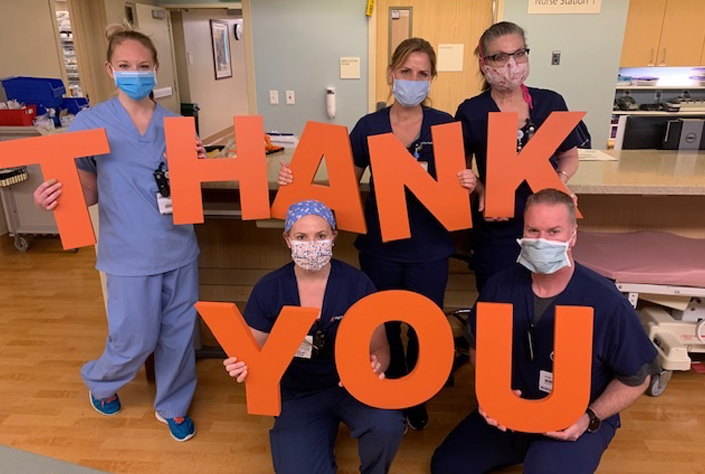 Staff holding thank you sign.